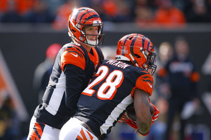 Cincinnati Bengals quarterback Ryan Finley, left, hands off the ball to running back Joe Mixon (28) during the first half an NFL football game against the Pittsburgh Steelers, Sunday, Nov. 24, 2019, in Cincinnati. (AP Photo/Gary Landers)