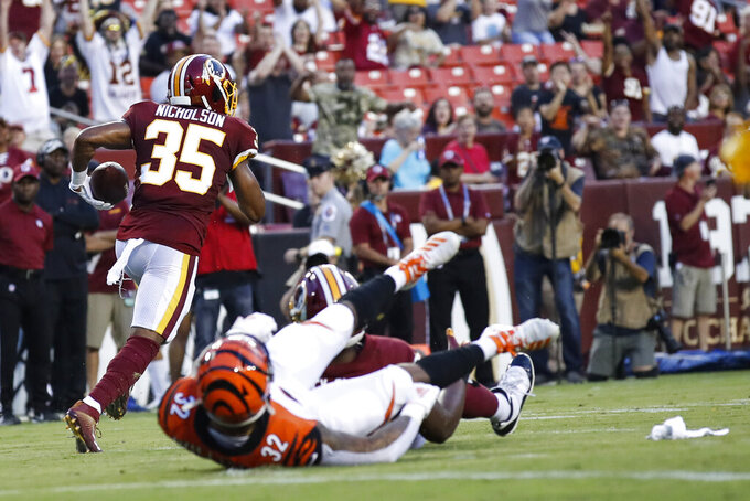 Washington Redskins safety Montae Nicholson (35) runs for a touchdown after his interception, next to Cincinnati Bengals running back Trayveon Williams (32) during the first half of an NFL preseason football game Thursday, Aug. 15, 2019, in Landover, Md. (AP Photo/Alex Brandon)