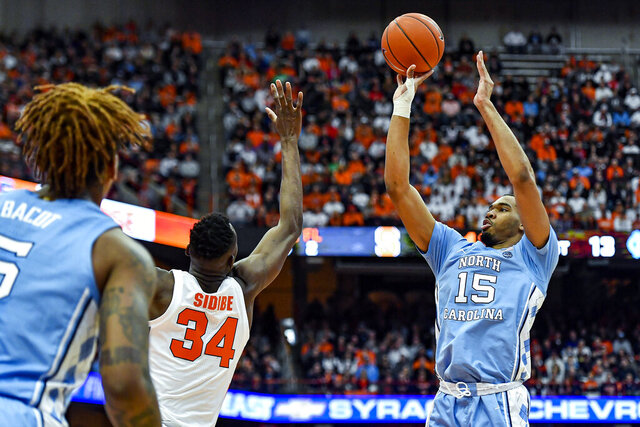 North Carolina forward Garrison Brooks (15) takes a shot over Syracuse forward Bourama Sidibe (34) during the first half of an NCAA college basketball game in Syracuse, N.Y., Saturday, Feb. 29, 2020. (AP Photo/Adrian Kraus)