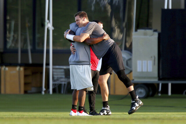 Tampa Bay Buccaneers running back LeSean McCoy, left, gets a hug from quarterback Tom Brady during NFL football training camp, Tuesday, Aug. 4, 2020, in Tampa. (Douglas R. Clifford/Tampa Bay Times via AP)