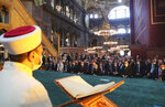 An imam reads from the Quran, Islams holy book, as dignitaries including Turkey's President Recep Tayyip Erdogan take part in Friday prayers in Hagia Sophia, at the historic Sultanahmet district of Istanbul, Friday, July 24, 2020. Fulfilling a dream of his Islamic-oriented youth, Erdogan joined hundreds of worshipers for the first Muslim prayers in 86 years inside the Istanbul landmark that served as one of Christendom's most significant cathedrals, a mosque and a museum before its conversion back into a Muslim place of worship. The conversion of the edifice, has led to an international outcry. (Turkish Presidency via AP, Pool)