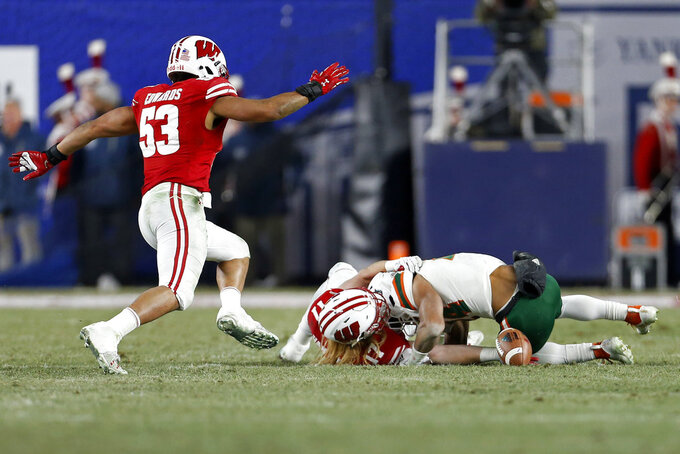 Miami running back Travis Homer fumbles the ball while being tackled by Wisconsin linebacker Andrew Van Ginkel during the first half of the Pinstripe Bowl NCAA college football game Thursday, Dec. 27, 2018, in New York. Wisconsin recovered the fumble. (AP Photo/Adam Hunger)