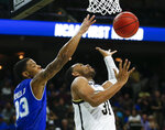 Seton Hall's Shavar Reynolds, left, partially blocks a shot by Wofford's Donovan Theme-Love during the first half of a first-round game in the NCAA men's college basketball tournament in Jacksonville, Fla., Thursday, March 21, 2019. (AP Photo/Stephen B. Morton)