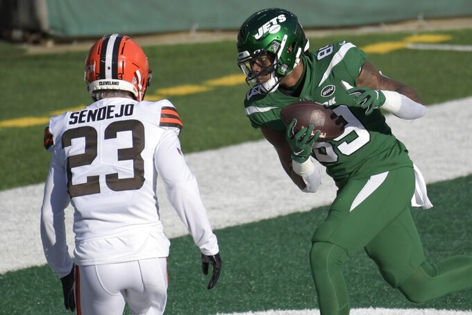 New York Jets' Chris Herndon (89) catches a pass for a touchdown in front of Cleveland Browns' Andrew Sendejo (23) during the first half of an NFL football game Sunday, Dec. 27, 2020, in East Rutherford, N.J. (AP Photo/Bill Kostroun)