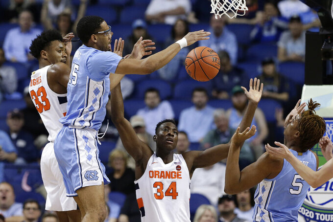 North Carolina forward Garrison Brooks (15) and Syracuse forward Elijah Hughes (33) reach for the ball while North Carolina forward Armando Bacot (5) and Syracuse forward Bourama Sidibe (34) look on during the first half of an NCAA college basketball game at the Atlantic Coast Conference tournament in Greensboro, N.C., Wednesday, March 11, 2020. (AP Photo/Gerry Broome)
