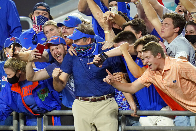 Florida head coach Dan Mullen, center, celebrate with fans in the stands after the Gators defeated Georgia in an NCAA college football game, Saturday, Nov. 7, 2020, in Jacksonville, Fla. (AP Photo/John Raoux)