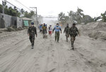 Police and military men walk along a road covered in volcanic ash at a village beside Taal volcano where residents have evacuated to safer ground in Agoncillo, Batangas province, southern Philippines on Saturday Jan. 18, 2020. The Taal volcano near the Philippine capital emitted more ash clouds Saturday, posing the threat of another eruption. (AP Photo/Aaron Favila)