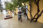 Owner Alex Yarosheno holds onto a tree as the Russian River flows through Surrey Resort in Guerneville, Calif., Friday, Feb. 15, 2019. Streets and low-lying areas flooded as the Russian River swelled above its banks Friday. (AP Photo/Josh Edelson)