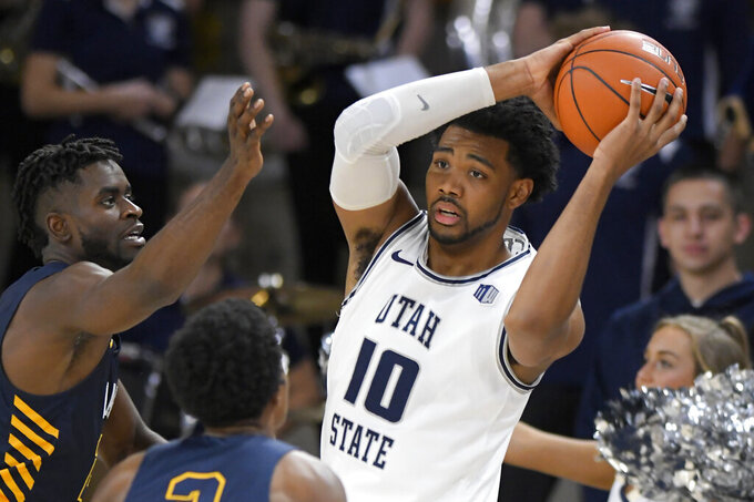 Utah State forward Alphonso Anderson (10) looks to pass the ball as North Carolina A&T forward Ronald Jackson, left, and guard Fred Cleveland Jr. defend during the first half of an NCAA college basketball game Friday, Nov. 15, 2019, in Logan, Utah. (AP Photo/Eli Lucero)