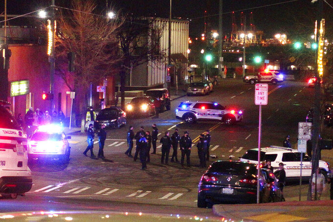 Tacoma Police and other law enforcement officers stand in an intersection near the site of a car crash Saturday, Jan. 23, 2021, in downtown Tacoma, Wash. At least one person was injured when a police car plowed through a crowd of people Saturday night who were watching a downtown street race, the Tacoma News-Tribune reported. (AP Photo/Ted S. Warren)
