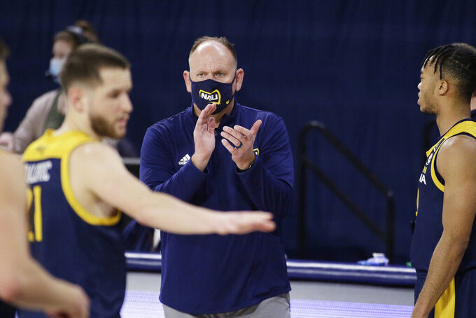 FILE - In this Monday, Dec. 28, 2020 file photo, Northern Arizona coach Shane Burcar encourages his players during the second half of an NCAA college basketball game against Gonzaga in Spokane, Wash. Northern Arizona built enough momentum two years ago to get the interim tag removed from coach Shane Burcar's title. A pandemic-altered 2019-20 season filled with stops and starts set the Lumberjacks back, even if they did finish strong. Now that college basketball is headed toward what appears to be a somewhat-normal return, Burcar and the 'Jacks are poised to turn the momentum churning upward again.(AP Photo/Young Kwak, File)