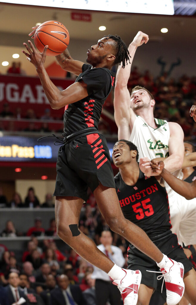 Houston guard Dejon Jarreau, left, pulls down a rebound in front of forward Brison Gresham, center, and South Florida forward Antun Maricevic, right, during the first half of an NCAA college basketball game Saturday, Feb. 23, 2019, in Houston. (AP Photo/Michael Wyke)