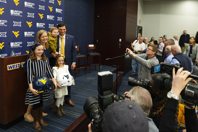 West Virginia University's new NCAA college football head coach Neal Brown poses for a photo with his wife Brooke, their two daughters Adalyn and Anslee, and their son Dax after a press conference in Morgantown, W.Va., Thursday, Jan. 10, 2019. (Craig Hudson/The Charleston Gazette-Mail via AP)