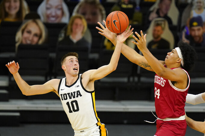 Iowa guard Joe Wieskamp (10) fights for a loose ball with Rutgers guard Ron Harper Jr., right, during the second half of an NCAA college basketball game, Wednesday, Feb. 10, 2021, in Iowa City, Iowa. (AP Photo/Charlie Neibergall)