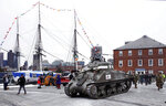 World War II tank gunner Clarence Smoyer sits atop a tank as he passes the historic frigate U.S.S. Constitution at the Charlestown Naval Shipyard in Boston, Wednesday, Feb. 20, 2019. The 95-year-old veteran was surprised with a ride through the streets of Boston in a Sherman tank, one of the tanks most widely used by the U.S. during the war. (AP Photo/Charles Krupa)