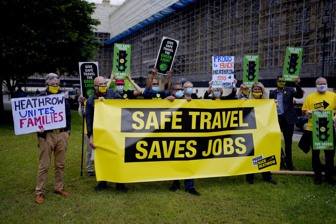 People who work in the UK aviation and travel industry take part in a 'Travel Day of Action' protest across the street from the Houses of Parliament in London, Wednesday, June 23, 2021. The protest on Wednesday was attended by people from across the UK aviation and travel industry calling on the British government to safely reopen international travel for the peak summer season to protect travel jobs and businesses amidst Britain's widely praised rollout of coronavirus vaccines. (AP Photo/Matt Dunham)