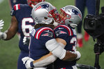 New England Patriots quarterback Cam Newton, left, celebrates his touchdown pass to running back Rex Burkhead, right, in the first half of an NFL football game against the Baltimore Ravens, Sunday, Nov. 15, 2020, in Foxborough, Mass. (AP Photo/Elise Amendola)