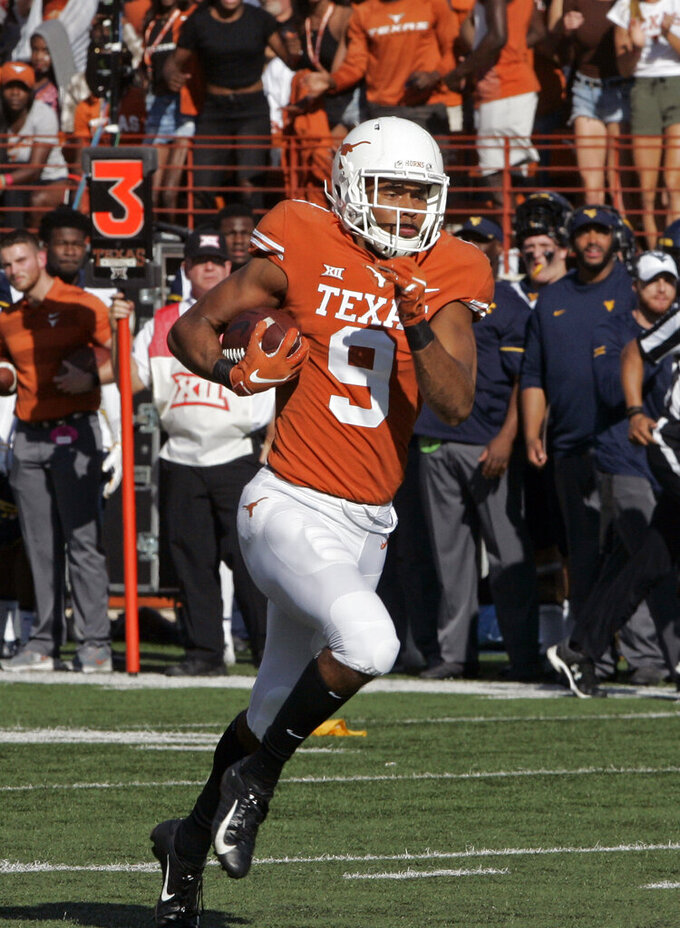 Texas receiver Collin Johnson runs after a catch during the first half of an NCAA college football game against West Virginia, Saturday, Nov. 3, 2018, in Austin, Texas. Johnson's touchdown was called back on a Texas offensive pass interference call. (AP Photo/Michael Thomas)