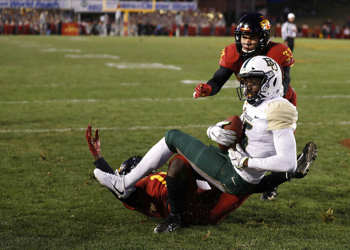 Baylor wide receiver Denzel Mims, front top, makes a catch for a touchdown despite defensive efforts by Iowa State defensive backs Brian Peavy, bottom, and Braxton Lewis, back top, during the second half of an NCAA college football game, Saturday, Nov. 10, 2018, in Ames, Iowa. (AP Photo/Matthew Putney)