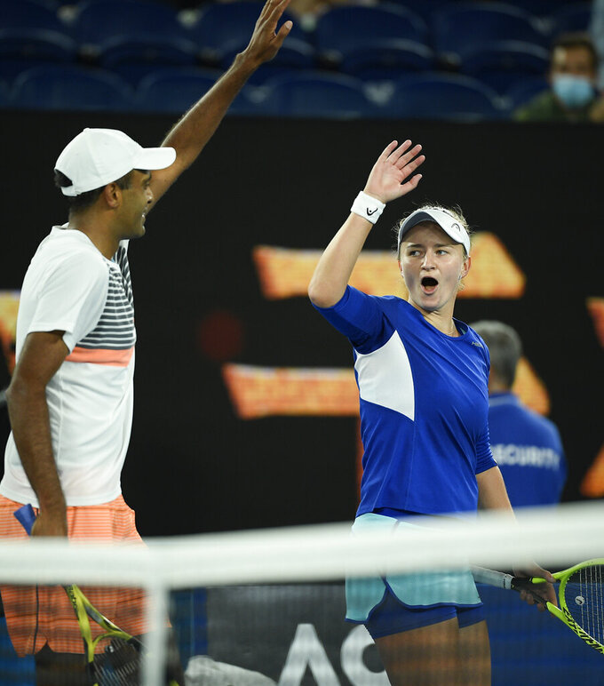 Rajeev Ram of the US and Barbora Krejcikova of the Czech Republic celebrate after defeating Australia's Samantha Stosur and Matthew Ebden in the mixed doubles final at the Australian Open tennis championship in Melbourne, Australia, Saturday, Feb. 20, 2021.(AP Photo/Andy Brownbill)