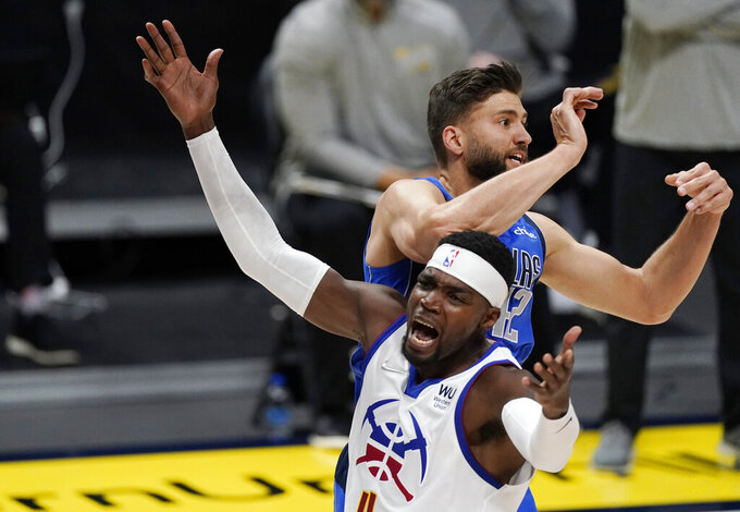 Denver Nuggets forward Paul Millsap, front, reacts to taking a elbow to the head from Dallas Mavericks forward Maxi Kleber while vying for a rebound during the first half of an NBA basketball game Saturday, March 13, 2021, in Denver. (AP Photo/David Zalubowski)