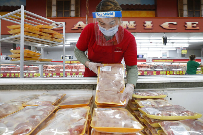 FILE - In this April 29, 2020 file photo, a worker restocks chicken in the meat product section at a grocery store in Dallas. Rising prices for a variety of commodities are contributing to a jump in prices at the consumer level in 2021, with Americans paying more for meat, gasoline, items they keep in their homes and even the homes themselves. (AP Photo/LM Otero)