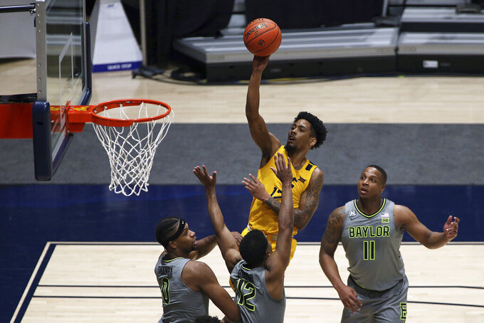 West Virginia guard Taz Sherman (12) shoots while defended by Baylor forward Flo Thamba (0) and guards Jared Butler (12) and Mark Vital (11) during the first half of an NCAA college basketball game Tuesday, March 2, 2021, in Morgantown, W.Va. (AP Photo/Kathleen Batten)