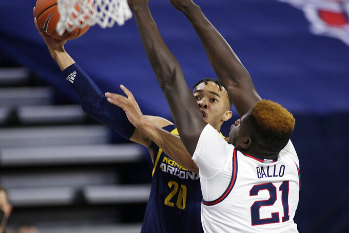 Northern Arizona guard Cameron Shelton (20) shoots next to Gonzaga center Oumar Ballo (21) during the first half of an NCAA college basketball game in Spokane, Wash., Monday, Dec. 28, 2020. (AP Photo/Young Kwak)