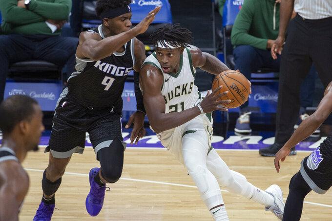Sacramento Kings guard Terrence Davis (9) defends against Milwaukee Bucks guard Jrue Holiday (21) during the second half of an NBA basketball game in Sacramento, Calif., Saturday, April 3, 2021. The Bucks won 129-128. (AP Photo/Randall Benton)