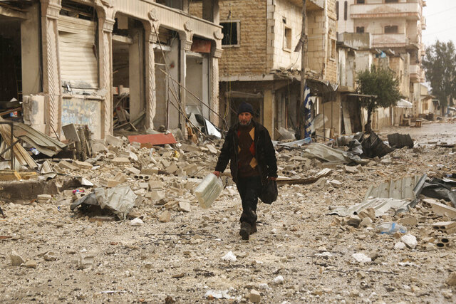 A man carries his belongings through a street destroyed in recent bombings by the Syrian government forces in the town of Sarmin, in Idblib province, Syria, Friday, Feb. 7, 2020. The Syrian government, backed by its ally Russia, has kept up a military offensive in Idlib province, aimed at securing a strategic highway that runs along rebel-controlled territory. President Bashar Assad's forces have seized dozens of rebel-held towns and villages in the past two months, displacing hundreds of people in the process. (AP Photo/Ghaith Alsayed)