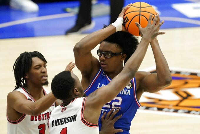 Western Kentucky's Jordan Rawls (3) and Josh Anderson, front, defend as Louisiana Tech forward Isaiah Crawford attempts to pass the ball in the first half of an NCAA college basketball game in the quarterfinals of the NIT, Thursday, March 25, 2021, in Frisco, Texas. (AP Photo/Tony Gutierrez)
