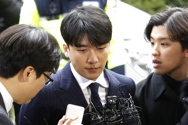 FILE - In this March 14, 2019, file photo, Seungri, center, member of a popular K-pop boy band Big Bang, arrives at the Seoul Metropolitan Police Agency in Seoul, South Korea. The state-run Military Manpower Administration said Tuesday, Feb. 4, 2020, it sent Seungri documents asking him to carry out 21 months of mandatory military service, a requirement for all able bodied men in South Korea, because prosecutors ended their investigation on him. (AP Photo/Ahn Young-joon, File)