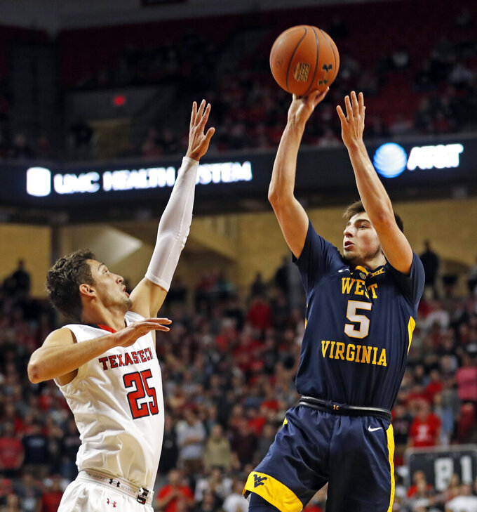 West Virginia's Jordan McCabe (5) shoots the ball over Texas Tech's Davide Moretti (25) during the first half of an NCAA college basketball game Monday, Feb. 4, 2019, in Lubbock, Texas. (AP Photo/Brad Tollefson)