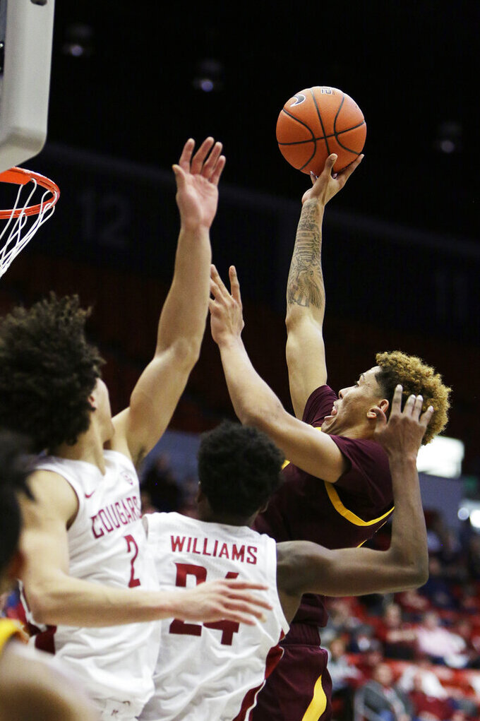 Arizona State forward Jalen Graham, right, shoots over Washington State forward CJ Elleby, left, and guard Noah Williams during the second half of an NCAA college basketball game in Pullman, Wash., Wednesday, Jan. 29, 2020. Washington State won 67-65. (AP Photo/Young Kwak)