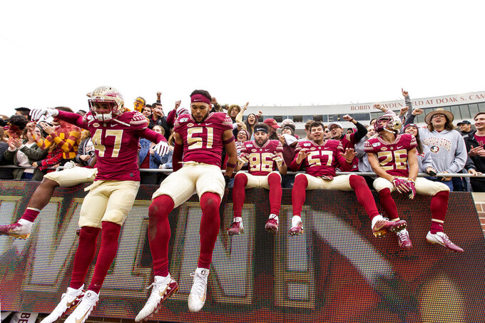 Florida State players dismount the wall after celebrating with their fans after defeating against Alabama State 49-12 in an NCAA college football game in Tallahassee, Fla., Saturday, Nov. 16, 2019. (AP Photo/Mark Wallheiser)