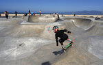 A young skateboarder takes a run at a sparsely crowded Venice beach skateboard park ahead of the 4th of July holiday on Friday, July 3, 2020 in Los Angeles. The Los Angeles County Department of Public Health is ordering L.A. County beaches closed from July 3 through July 6, to prevent dangerous crowding that results in the spread of deadly COVID-19. California's governor is urging people to wear masks and skip Fourth of July family gatherings as the state's coronavirus tally rises. (AP Photo/Richard Vogel)