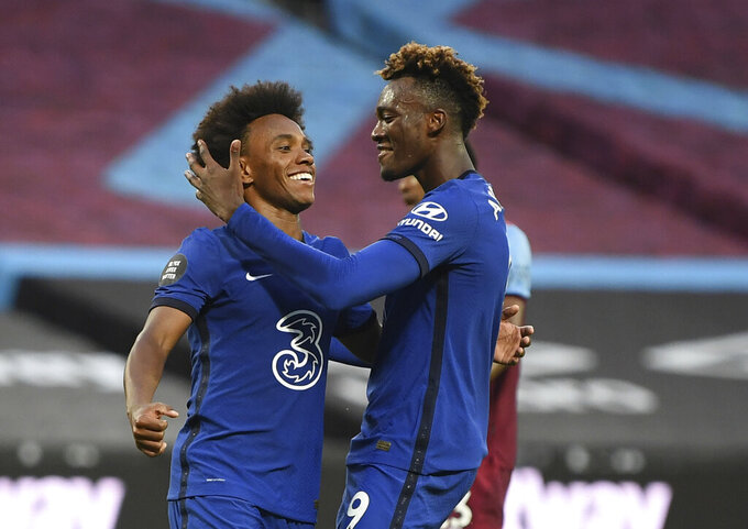 Chelsea's Willian, left , celebrates with teammate Chelsea's Willian after scoring the opening goal of the game from the penalty spot during the English Premier League soccer match between West Ham United and Chelsea at the London Stadium stadium in London, Wednesday July 1, 2020. (Michael Regan/Pool via AP)