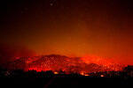 Flames dot a hill under a smoky sky from the Bobcat Fire in Juniper Hills, Calif., Friday, Sept. 18, 2020. (AP Photo/Ringo H.W. Chiu)