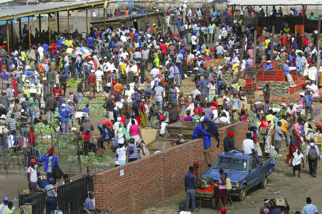 Hundreds of people buy goods at a fruit and vegetable market, despite a lockdown in an effort to curb the spread of the coronavirus,  in Harare, Zimbabwe, Tuesday April 7, 2020. (AP Photo/Tsvangirayi Mukwazhi)