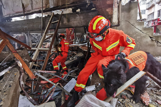 In this photo released by Xinhua News Agency, rescue workers using sniffer dogs to search for survivors in the aftermath of a gas explosion in Shiyan city in central China's Hubei Province on Sunday, June 13, 2021. At least a dozen people were killed and more seriously injured Sunday after a gas line explosion tore through the residential neighborhood in central China. (Xiao Yijiu/Xinhua via AP)