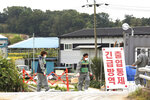 Quarantine officials stand guard as a precaution against African swine fever near a pig farm in Paju, South Korea, Friday, Sept. 20, 2019. South Korea said Friday that it is investigating two more suspected cases of African swine fever from farms near its border with North Korea, as fears grow over the spread of the illness that has decimated pig herds across Asia. The notice reads: