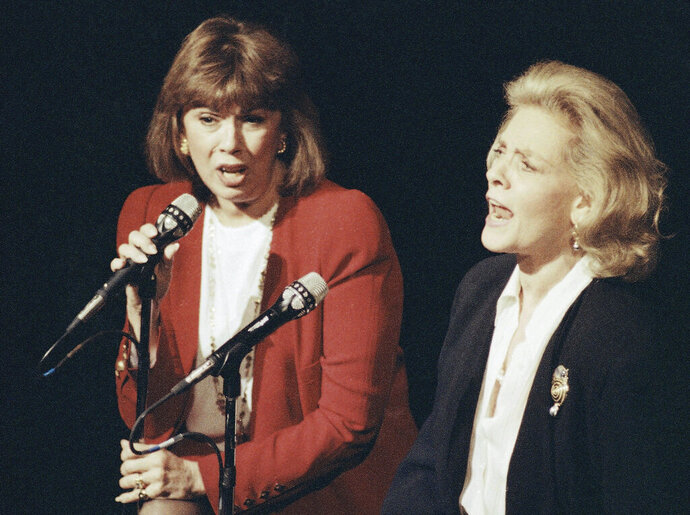 """FILE - In this Dec. 13, 1990, file photo, Phyllis Newman, left, and Lauren Bacall sing during a tribute to the late conductor Leonard Bernstein, at New York's Majestic Theatre. Newman, a Tony Award-winning Broadway veteran who became the first woman to host """"The Tonight Show"""" before turning her attention to fight for women's health, died Sunday, Sept. 15, 2019, in New York. She was 86. (AP Photo/Mark Lennihan, File)"""