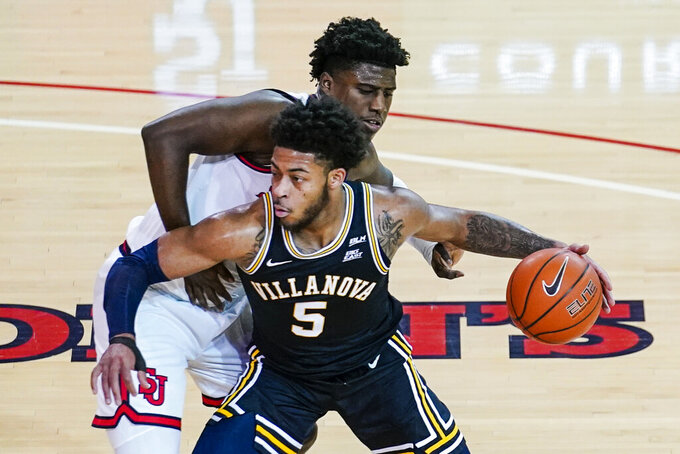 Villanova's Justin Moore (5) drives past St. John'sMarcellus Earlington during the first half of an NCAA college basketball game Wednesday, Feb. 3, 2021, in New York. (AP Photo/Frank Franklin II)