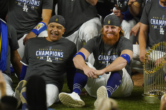 FILE - In this Oct. 27, 2020 file photo, Los Angeles Dodgers manager Dave Roberts and third baseman Justin Turner pose for a group picture after the Dodgers defeated the Tampa Bay Rays to win the baseball World Series in Arlington, Texas.  Roberts isn't sure Turner or former All-Star pitcher David Price will play with the Los Angeles Dodgers in 2021.(AP Photo/Eric Gay, File)