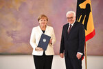 German president  Frank-Walter Steinmeier, right, and German chancellor Angela Merkel, left, pose at the presidential residence, Bellevue palace, in Berlin, Germany Wednesday, March 14, 2018, after Steinmeier handed over the letter of appointment. Germany's parliament elected Angela Merkel for her fourth term as chancellor on Wednesday, putting an end to nearly six months of political drift in Europe's biggest economy. (Bernd Von Jutrczenka/dpa via AP)