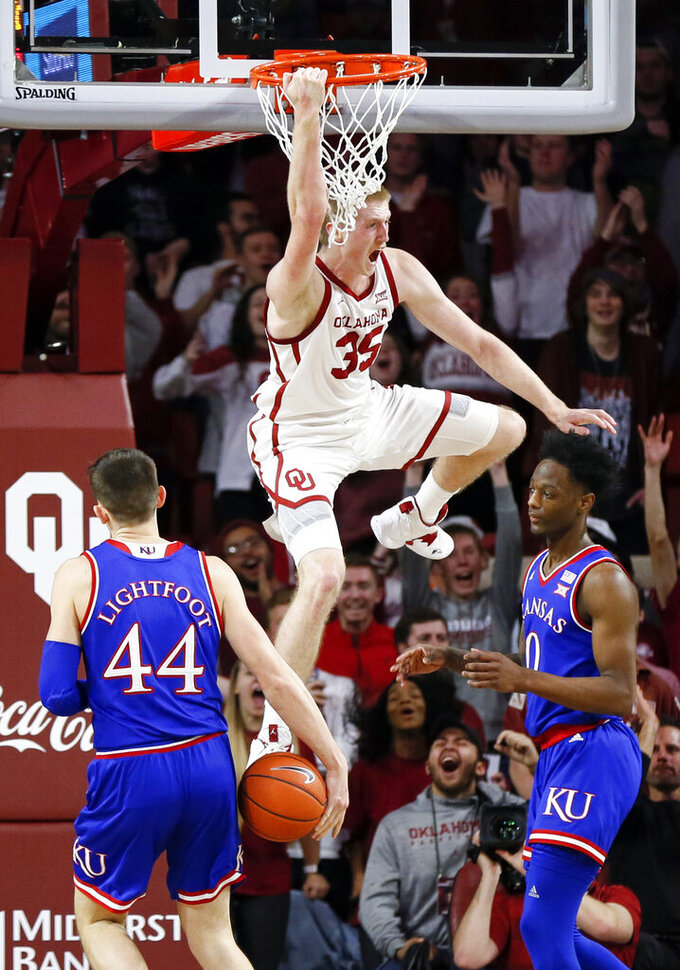 Oklahoma forward Brady Manek (35) reacts between Kansas forward Mitch Lightfoot (44) and guard Marcus Garrett (0) after a dunk in the first half of an NCAA college basketball game in Norman, Okla., Tuesday, March 5, 2019. (AP Photo/Nate Billings)
