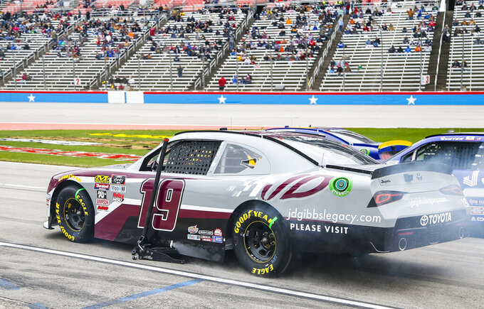 Brandon Jones leaves pit road with a jack stuck to his car during a NASCAR auto race at Texas Motor Speedway, Saturday, March 30, 2019, in Fort Worth, Texas. Jones would complete a lap before returning to his pit box to have the jack removed. (AP Photo/Brandon Wade)