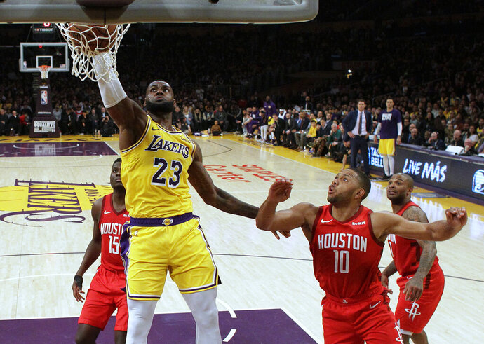 Los Angeles Lakers' LeBron James (23) dunks past Houston Rockets' Eric Gordon (10) during the second half of an NBA basketball game Thursday, Feb. 21, 2019, in Los Angeles. (AP Photo/Marcio Jose Sanchez)