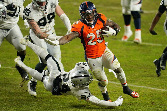 Denver Broncos running back Melvin Gordon (25) avoids a tackle by Las Vegas Raiders strong safety Johnathan Abram (24) to run it in for a touchdown during the second half of an NFL football game, Sunday, Jan. 3, 2021, in Denver. (AP Photo/Jack Dempsey)