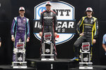 Will Power, center, of Australia, Romain Grosjean, left, of Switzerland, and Colton Herta pose with the trophies following an IndyCar auto race at Indianapolis Motor Speedway, Saturday, Aug. 14, 2021, in Indianapolis. Power won the race, Grosjean finished second and Herta finished third. (AP Photo/Darron Cummings)